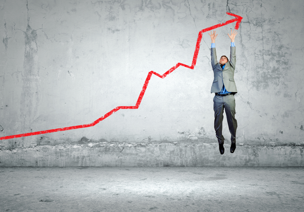 Image of young businessman jumping above graph-1