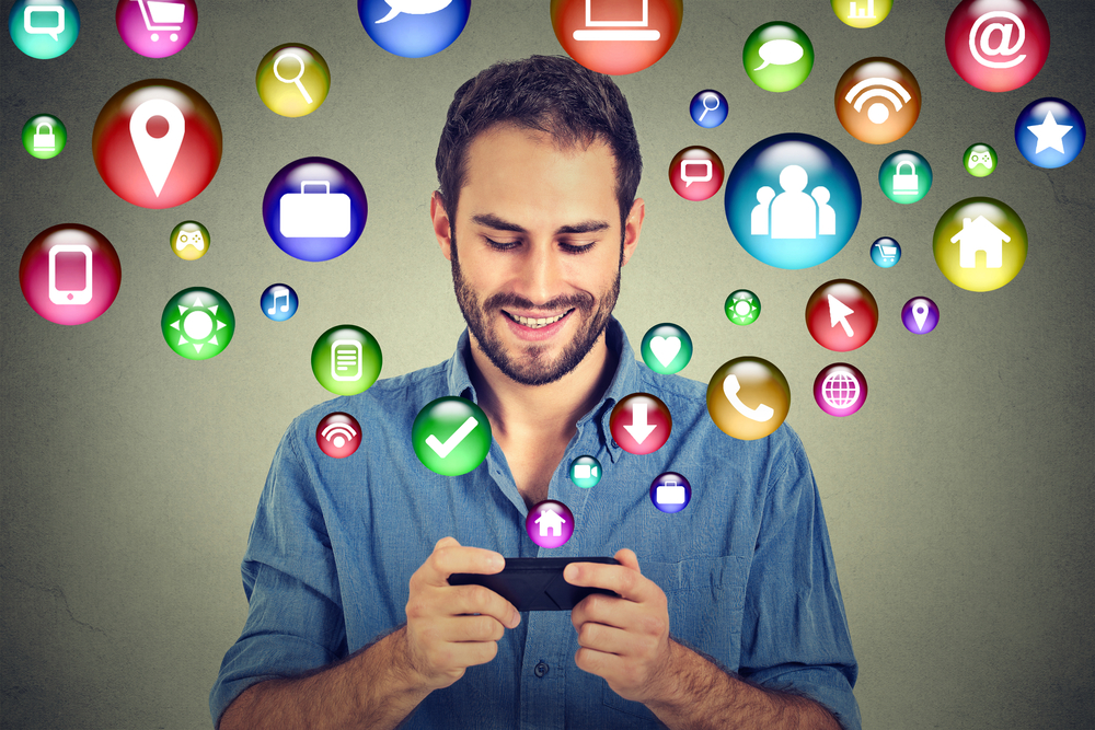 communication technology mobile phone high tech concept. Happy man using texting on smartphone social media application icons flying out of cellphone isolated grey wall background. 4g data plan-1